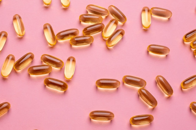 Vitamine omega 3 6 9 fischöl, vitamin d auf einem rosa