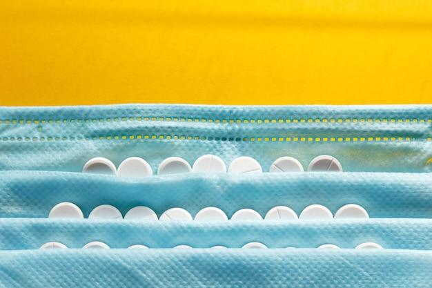 Vitamine und arztmaske, corona-virus-schutzkonzept auf gelber atemwegsmaske und pillen. coronavirus-, krankenhaus- oder umweltverschmutzung schützt die gesichtsmaskierung.