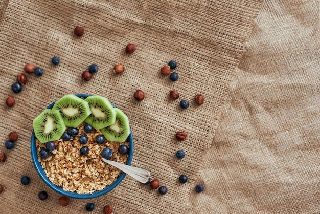 Vitaminfrühstück. draufsicht auf gesunde frühstückszerealien mit beeren, kürbiskernen, hafer und kiwi in schüssel auf isoliertem. gesunder snack oder frühstück am morgen.