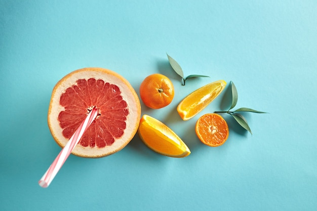 Vitamingetränk aus einer halben grapefruit, mandarine und orangenscheiben mit strohhalmen und blättern auf einem blauen papierhintergrund von oben. diätgetränk