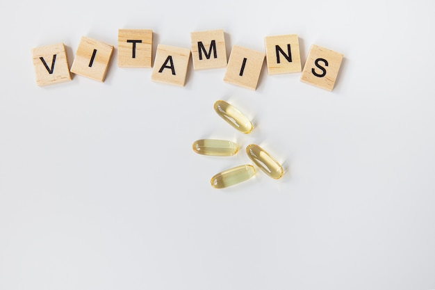 Vitamininschrift aus holzwürfeln. gesundheitspillen und nahrungsergänzungsmittel.