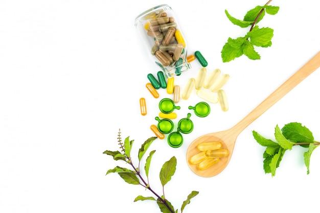 Vitaminkapsel oder organische kräutermedizin von der natur lokalisiert auf weißem hintergrund