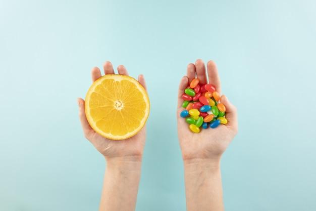 Vitaminpillen und frische orange in den händen, draufsicht. weibliche hände, die frucht in einer hand und bündel bonbons in der anderen im einfachen hintergrund halten