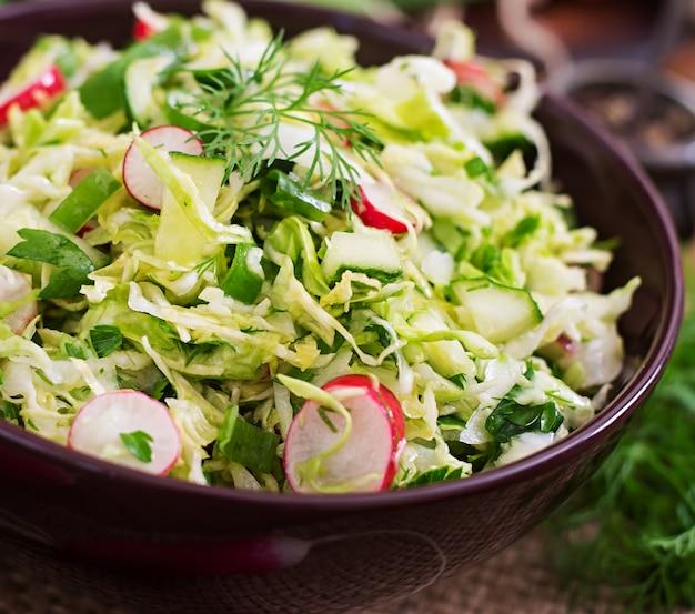 Vitaminsalat von jungem gemüse: kohl, radieschen, gurke und frische kräuter