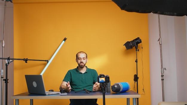 Vlogger-aufnahmetestimonial über mini-trepied für abonnenten. professionelle studio-video- und fotoausrüstungstechnologie für die arbeit, fotostudio-social-media-star und influencer