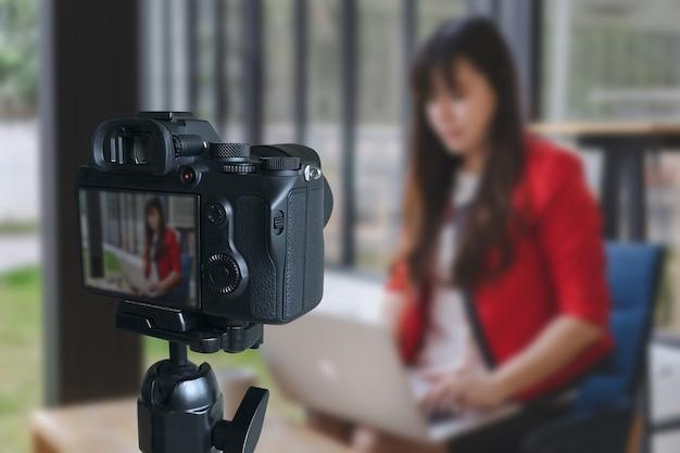 Vlogger benutzt den laptop, der ihren inhalt teilt, aufnahmevideo für ihre vlog tendenzen machend