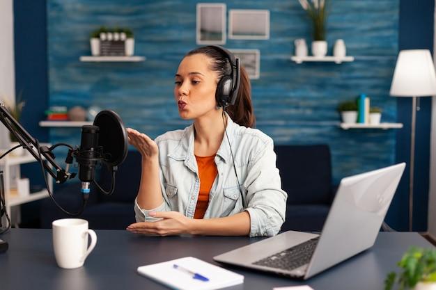 Vlogger, der einen fliegenden kuss gibt, während er einen täglichen online-videoblog erstellt. digitale influencer-aufzeichnung von talkshows im home-studio-broadcast mit kopfhörern, professionellem podcast-mikrofon und modernem laptop