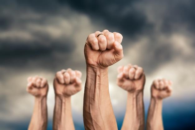 Völker erhoben faustluftkampf und sonnenlichteffekt, wettbewerb, teamwork-konzept,