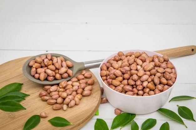 Völlig erdnüsse in der schüssel und im löffel auf weißer tabelle.