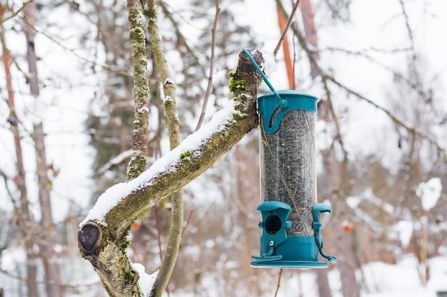 Vogelhäuschen auf einem ast mit nahrung, winter