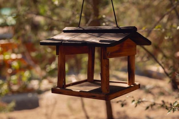 Vogelhäuschen-holzobjekt für samen, die an einem ast auf unkonzentriertem grünem naturparkhintergrund hängen