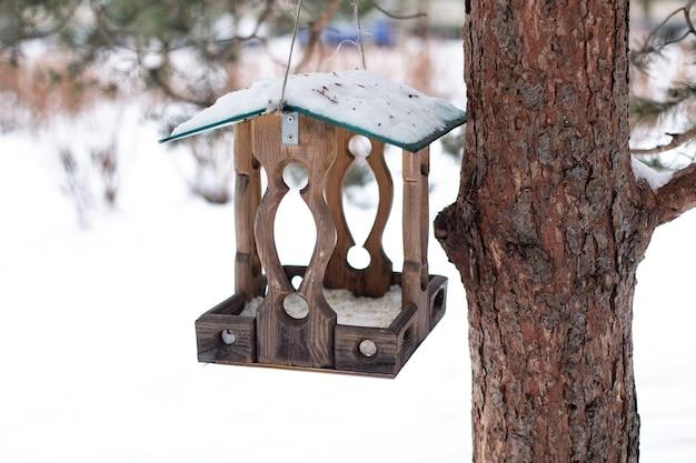 Vogelhäuschen mit körnern, die am baum im winterpark hängen