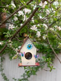 Vogelhaus, das an einem zweig eines blühenden baumes hängt. vogelpflege.