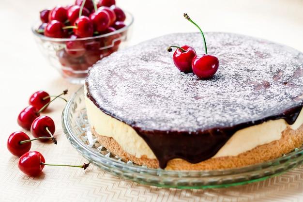 Vogelmilch-souffle-kuchen, mit schokoladenglasur überzogen und mit reifen saftigen kirschen dekoriert