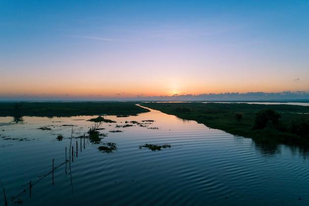 Vogelperspektive-brummen schoss vom schönen sonnenaufgang des landschaftssonnenlichts morgens über see in phatthalung thailand