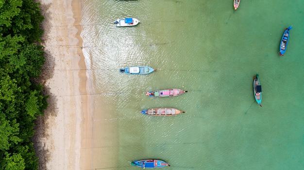 Vogelperspektive-brummen übersteigen unten von den thailändischen traditionellen longtail-fischerbooten im tropischen seeschönen strand