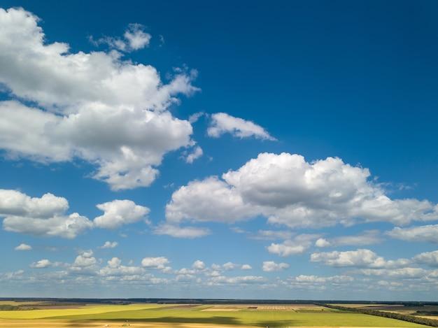 Vogelperspektive der bewölkten landschaft mit weißen wolken auf einem blauen himmelhintergrund und landwirtschaftlichen feldern in einem sommertag. luftaufnahme von der drohne.