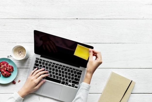 Vogelperspektive der frau, die einen computerlaptop auf holztischarbeitsplatzkonzept verwendet