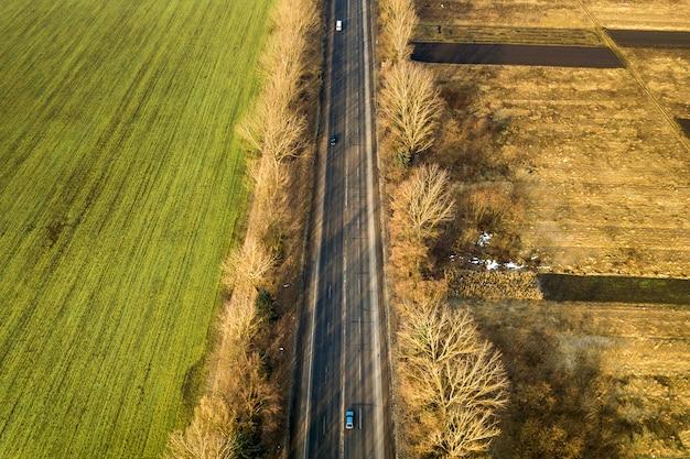 Vogelperspektive der geraden straße mit beweglichen autos, bäumen und grünfeldern am sonnigen tag. drohnenfotografie.