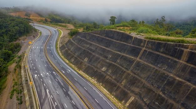 Vogelperspektive der szenischen straße auf der bergspitze des regenwaldes unter wolken oder nebel.