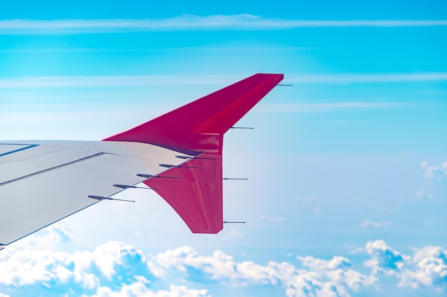 Vogelperspektive der wolke und des himmels und des landes mit flugzeugflügel vom flugzeugfenster