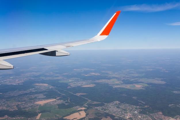 Vogelperspektive des blauen himmels der wolke und der flachen flügelansicht durch das flugzeugfenster.