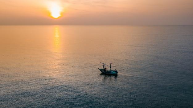 Vogelperspektive des einsamen fischerbootes des schattenbildes im meer während des morgensonnenaufgangs
