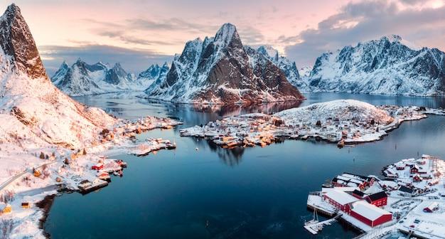 Vogelperspektive des fischerdorfes in umgebenem berg auf wintersaison