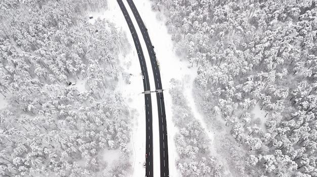 Vogelperspektive des schnees bedeckte straße im winterwald, den lkw, der vorbei, bewegungsunschärfe überschreitet