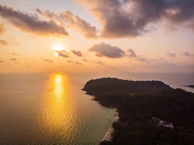 Vogelperspektive des schönen strandes und des meeres mit kokosnusspalme zur sonnenuntergangzeit