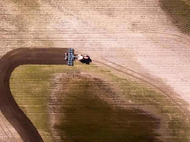 Vogelperspektive des traktors auf dem gebiet, landwirtschaftliche feldarbeit. traktorkultivierungsfeld, luftaufnahme