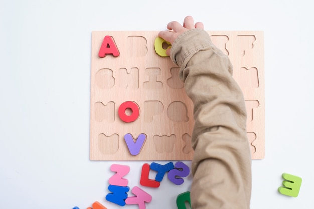 Vogelperspektive des vorschulkindes, des kindergartenjungen, der mit alphabetblöcken spielt, kinder, die englisch mit hölzernem pädagogischem abc-spielzeugrätsel lernen