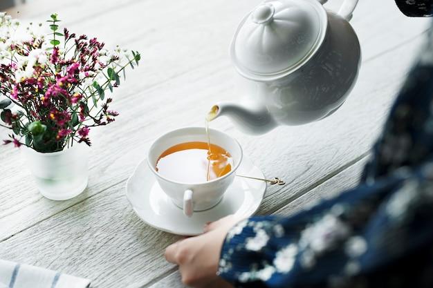 Vogelperspektive einer frau, die ein heißes teegetränk gießt