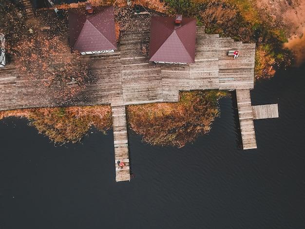 Vogelperspektive eines fischers mit einer angelrute auf dem pier, seeufer, herbstwald. finnland.