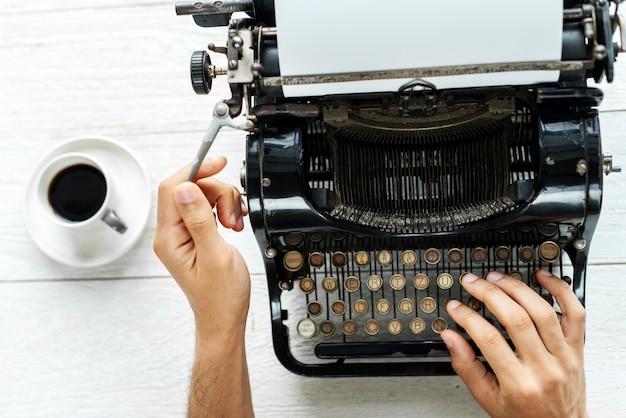 Vogelperspektive eines mannes, der auf einem retro- schreibmaschinenleeren papier schreibt