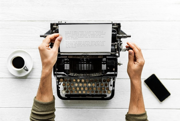 Vogelperspektive eines mannes, der auf einer retro- schreibmaschine schreibt