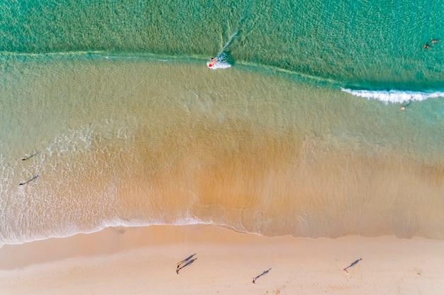 Vogelperspektive übersteigen unten fliegen über den türkisozean und -wellen, die den leeren sandigen strand am trauminsel-sommertag waschen