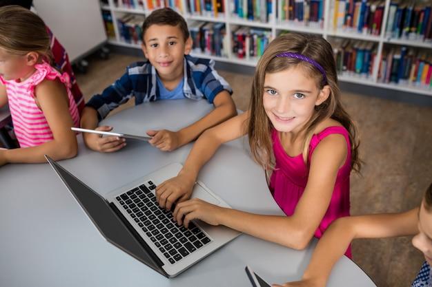 Vogelperspektive von den kindern, die laptop- und tabletten-pc verwenden