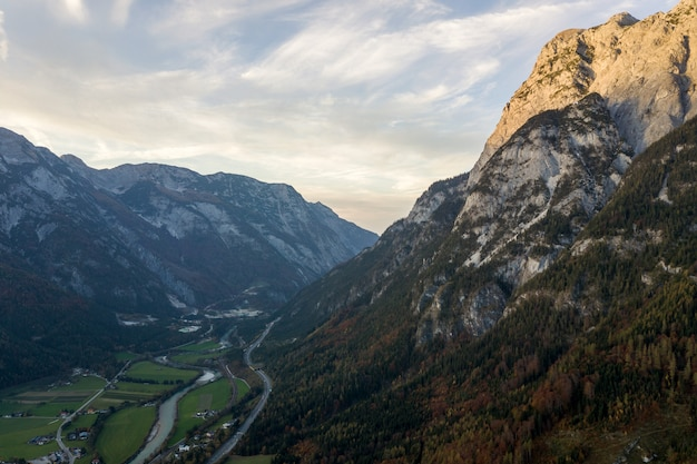 Vogelperspektive von den majestätischen europäischen alpenbergen bedeckt im immergrünen kiefernwald im herbst.