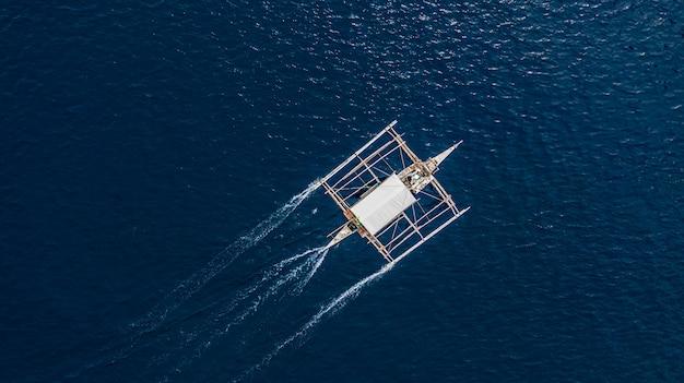 Vogelperspektive von den philippinischen booten, die auf klares blaues wasser schwimmen