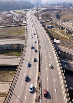 Vogelperspektive von der drohne der schnellstraßenasphaltstraße, die schnelle autos und spuren an einem sonnigen frühlingstag in der stadt kiew, ukraine bewegt.