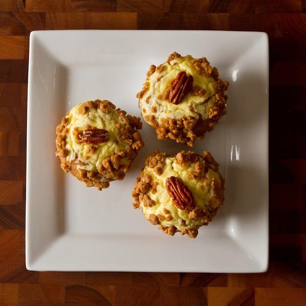 Vogelperspektive von drei orangefarbenen muffins mit zuckerguss und einer pekannuss auf einem weißen teller auf einem tisch