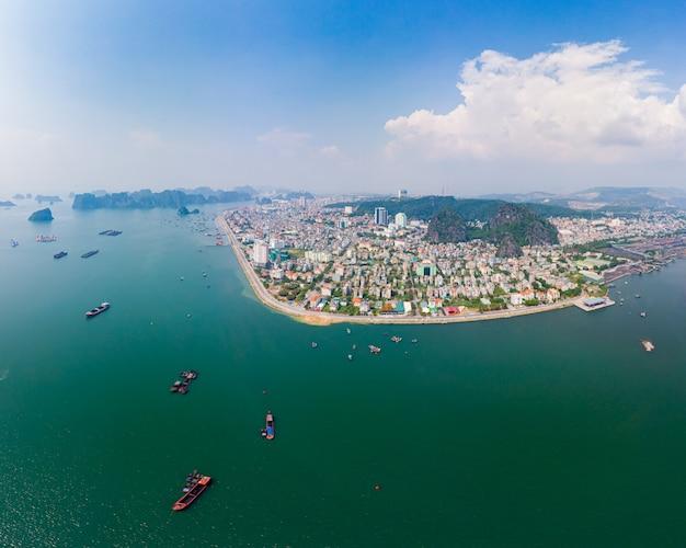 Vogelperspektive von ha long bay- und halong-stadtskylinen, von einzigartigen kalksteinfelseninseln und von karstbildungsspitzen im meer, berühmter tourismusbestimmungsort in vietnam. szenischer blauer himmel und nebel.