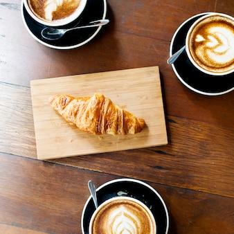 Vogelperspektive von kaffeetassen und von hörnchen auf holztisch
