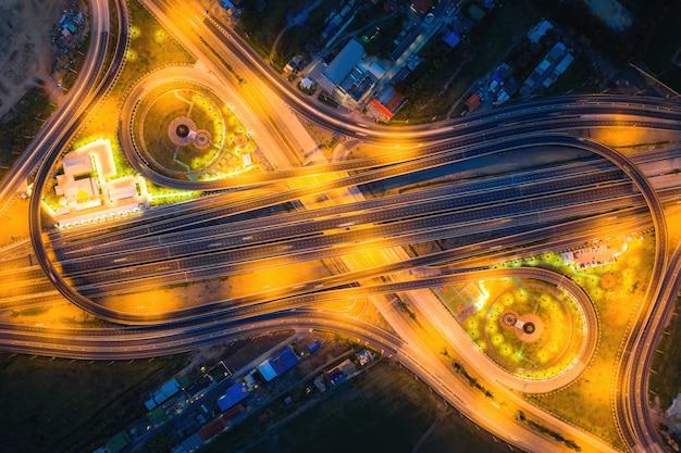 Vogelperspektive von landstraßenkreuzungen draufsicht der städtischen stadt, bangkok nachts, thailand. lichtspuren über straßenkreuzung, verkehrszusammenfassung und transportkonzept.