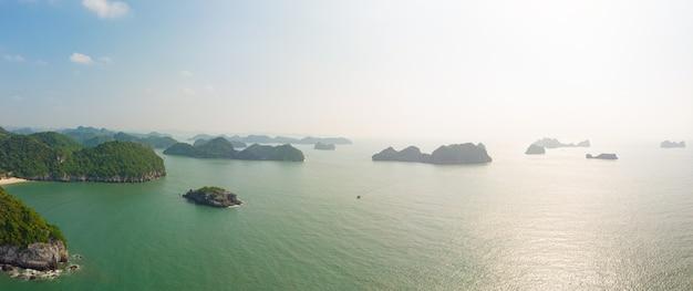 Vogelperspektive von langer bucht ha von cat ba-insel, berühmter tourismusbestimmungsort in vietnam. szenischer blauer himmel mit wolken, kalksteinfelsenspitzen im meer am horizont.