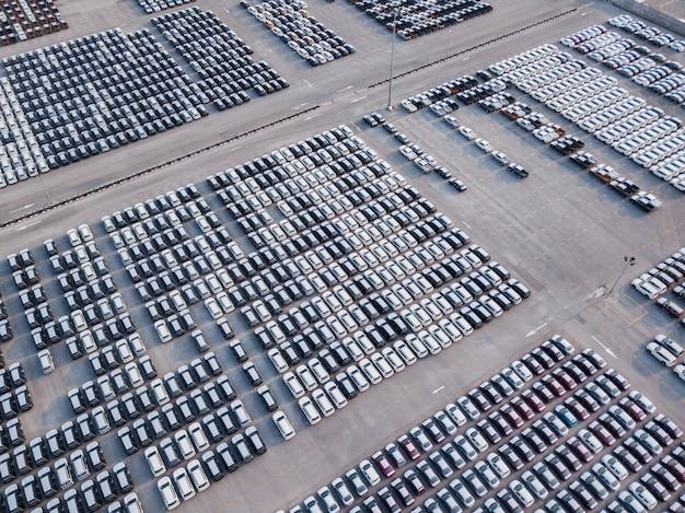 Vogelperspektive von neuen autos parkte am parkplatz der autofabrik. warten auf export und import am internationalen hafen.