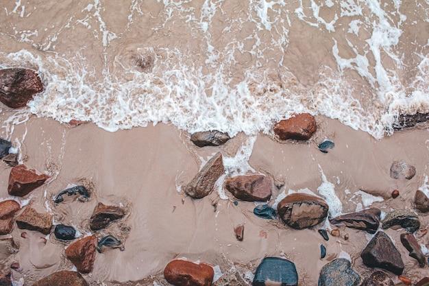 Vogelperspektive von zusammenstoßenden wellen auf steinen ansicht von oben, schöner naturhintergrund.