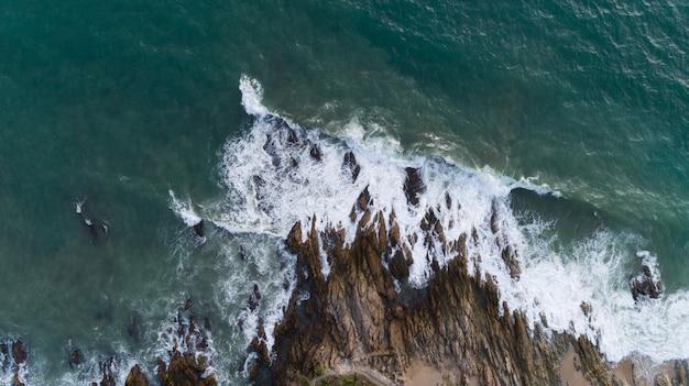 Vogelperspektivendrohne schoss vom meerblick landschaftlich vor strand mit der welle, die auf den felsen zusammenstößt