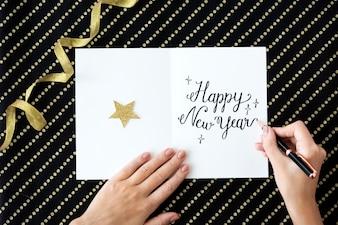 Vogelperspektivennahaufnahme der Hand, die Wunsch des neuen Jahres auf Karte schreibt